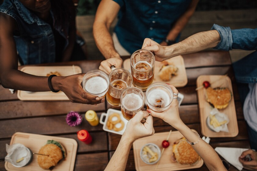 group of friends cheersing beer with burgers