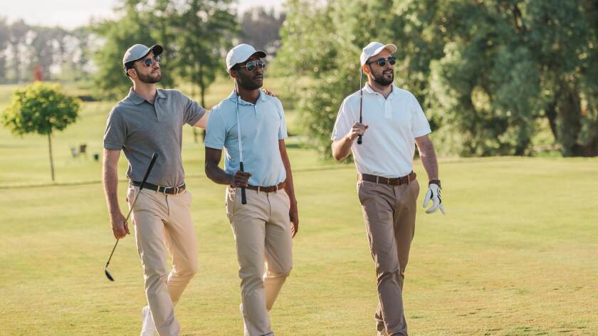 threesome group of male golfers walking on golf course