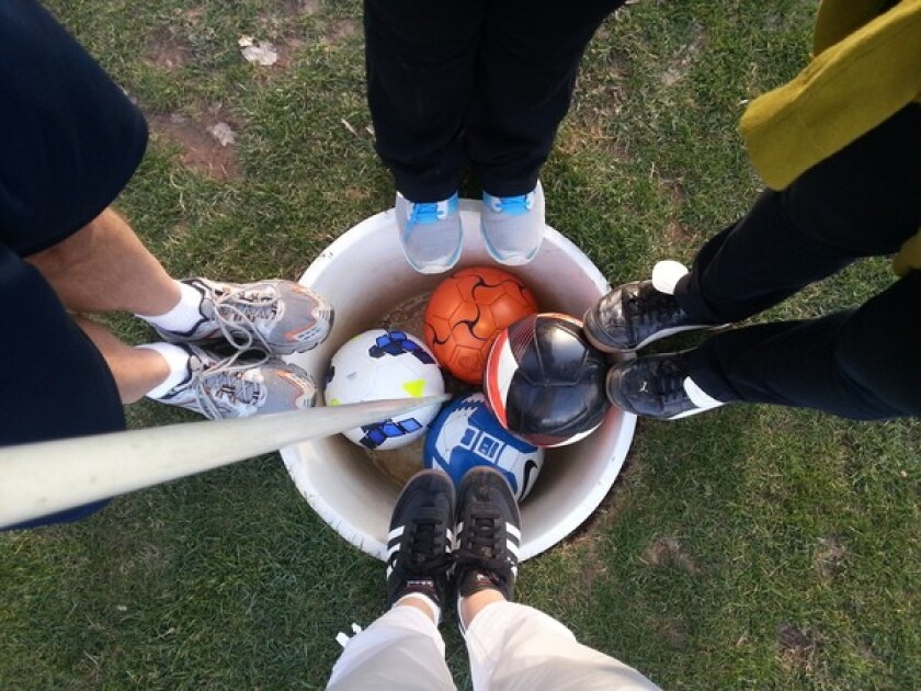 FootGolf - feet and soccer balls circled around hole