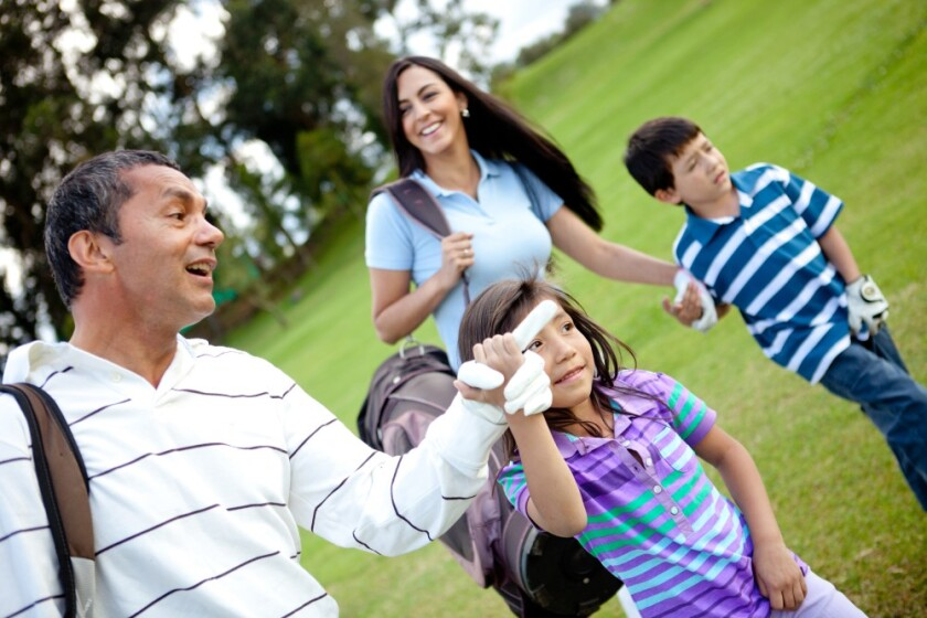 Family golfing - father mother daughter and son on the golf course