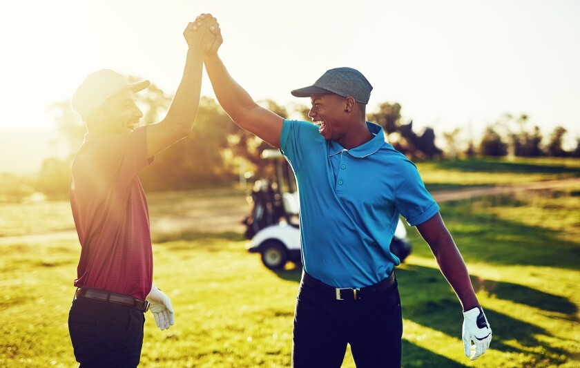 twosome golfers celebrate with high five on golf course with sunshine