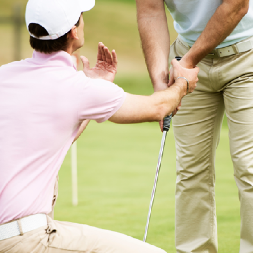 golf instructor teaching student grip