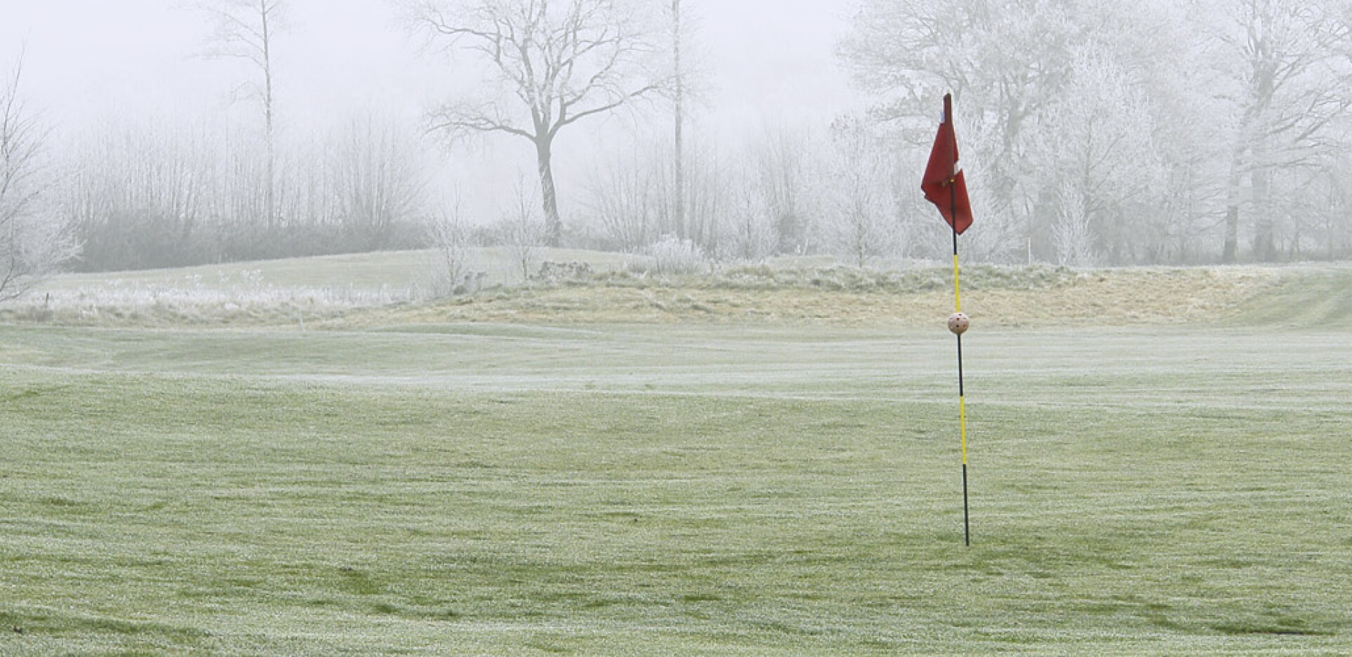 Golf Course Flag in Hole on Winter Course with Snow