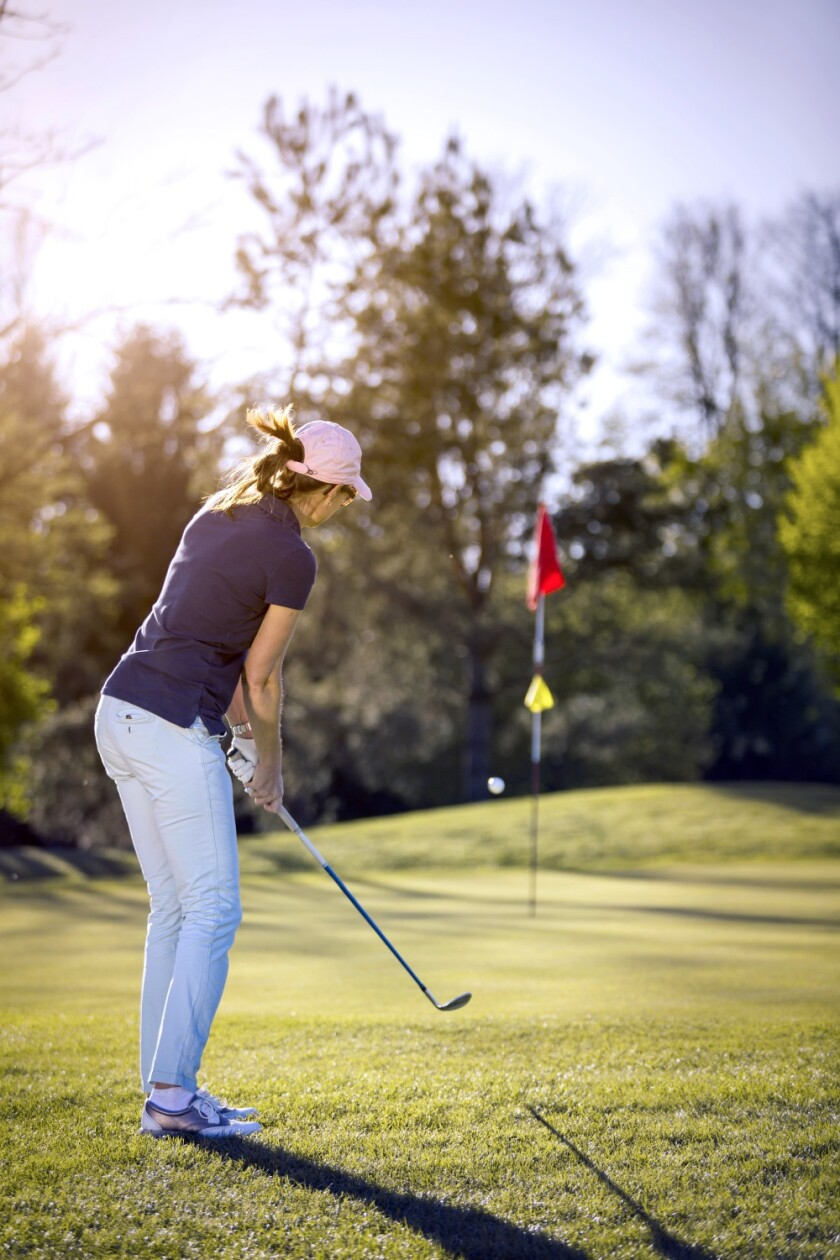 woman chipping onto green of golf course hole