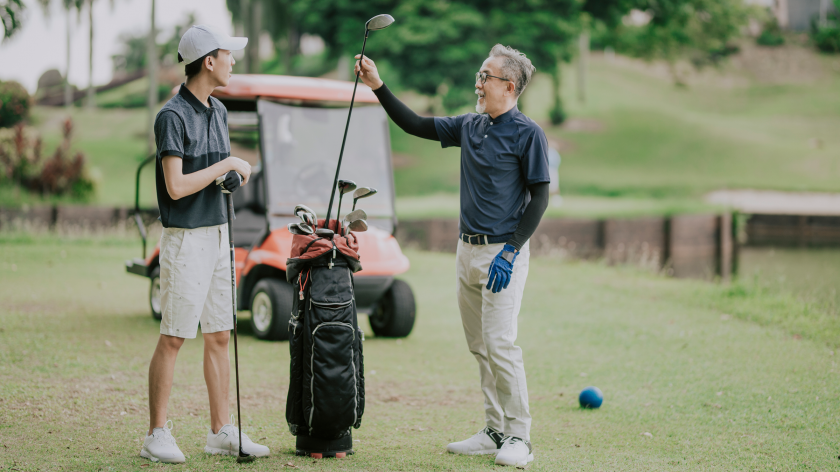 father son discussing golf game and choosing golf clubs at tee