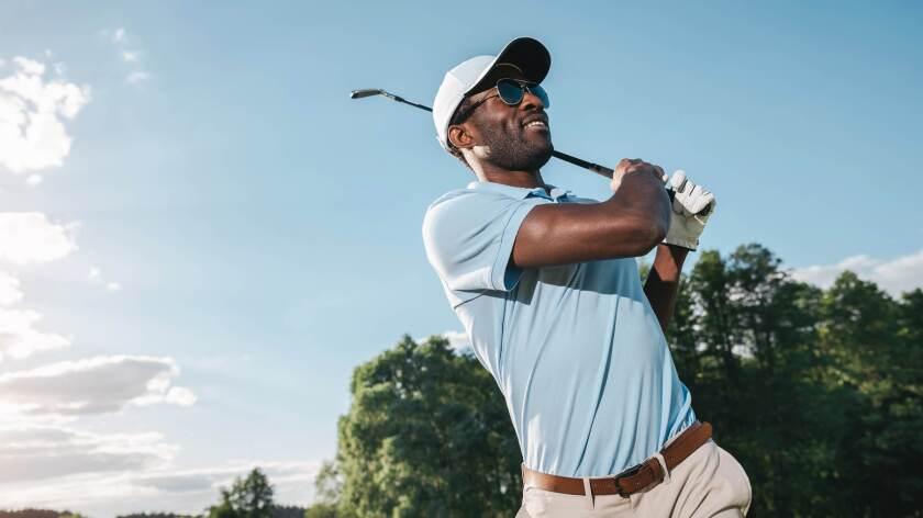 single male golfer on golf course swinging club in sunshine