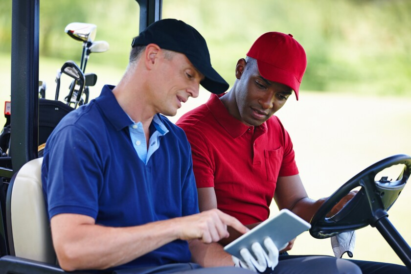 Shot of two men in a golf cart looking at a digital tablet