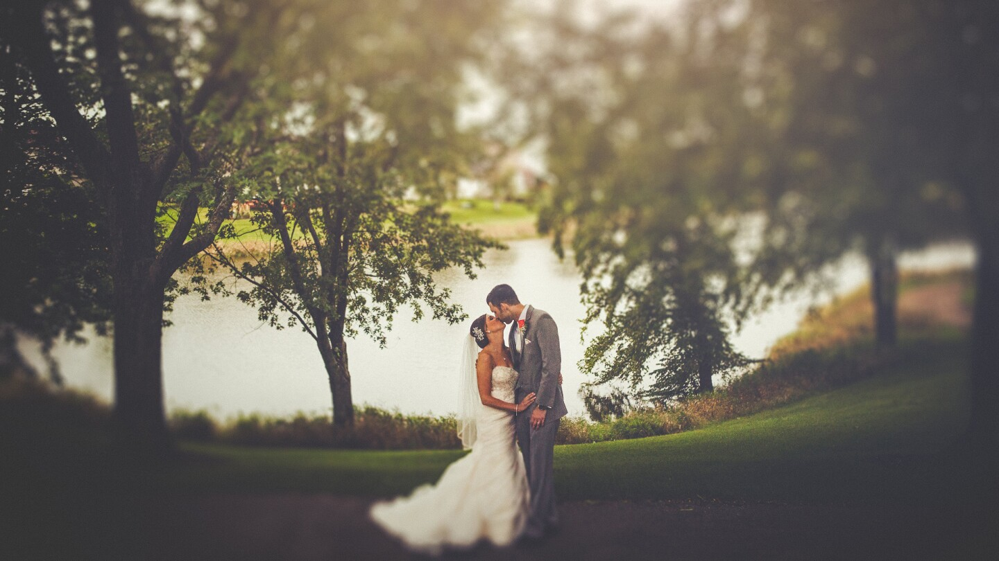 bride and groom kissing under giant tree by lake