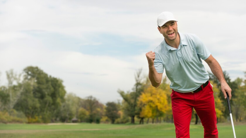 Male golfer holding club on golf course