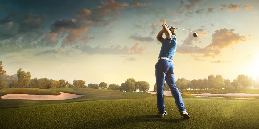 man swinging club on golf course at sunset