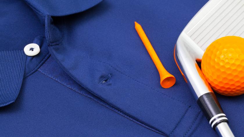 club ball and tee laying on blue polo shirt