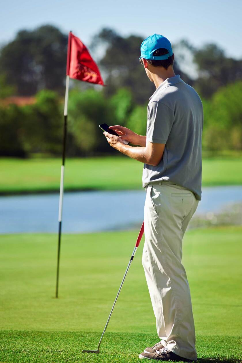 Guy holding mobile device on golf course