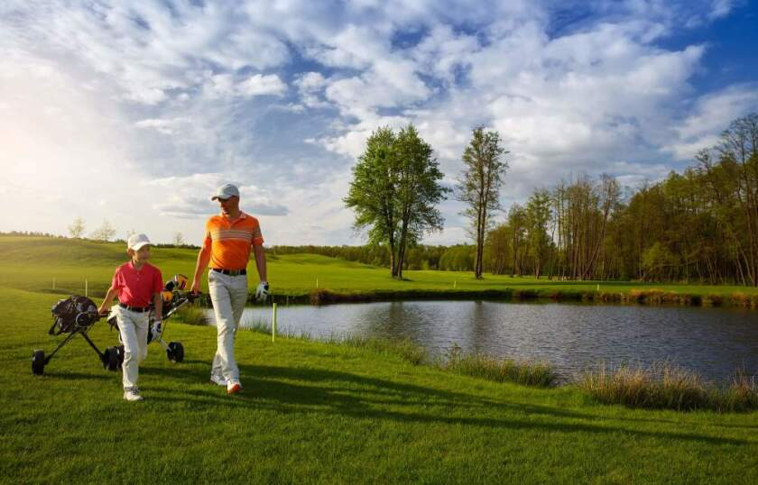 father son on course by pond