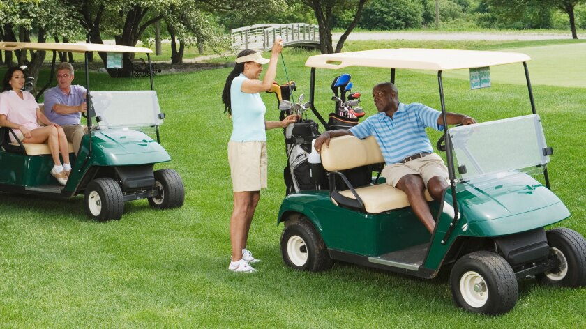 two couple golfers on course riding in golf carts