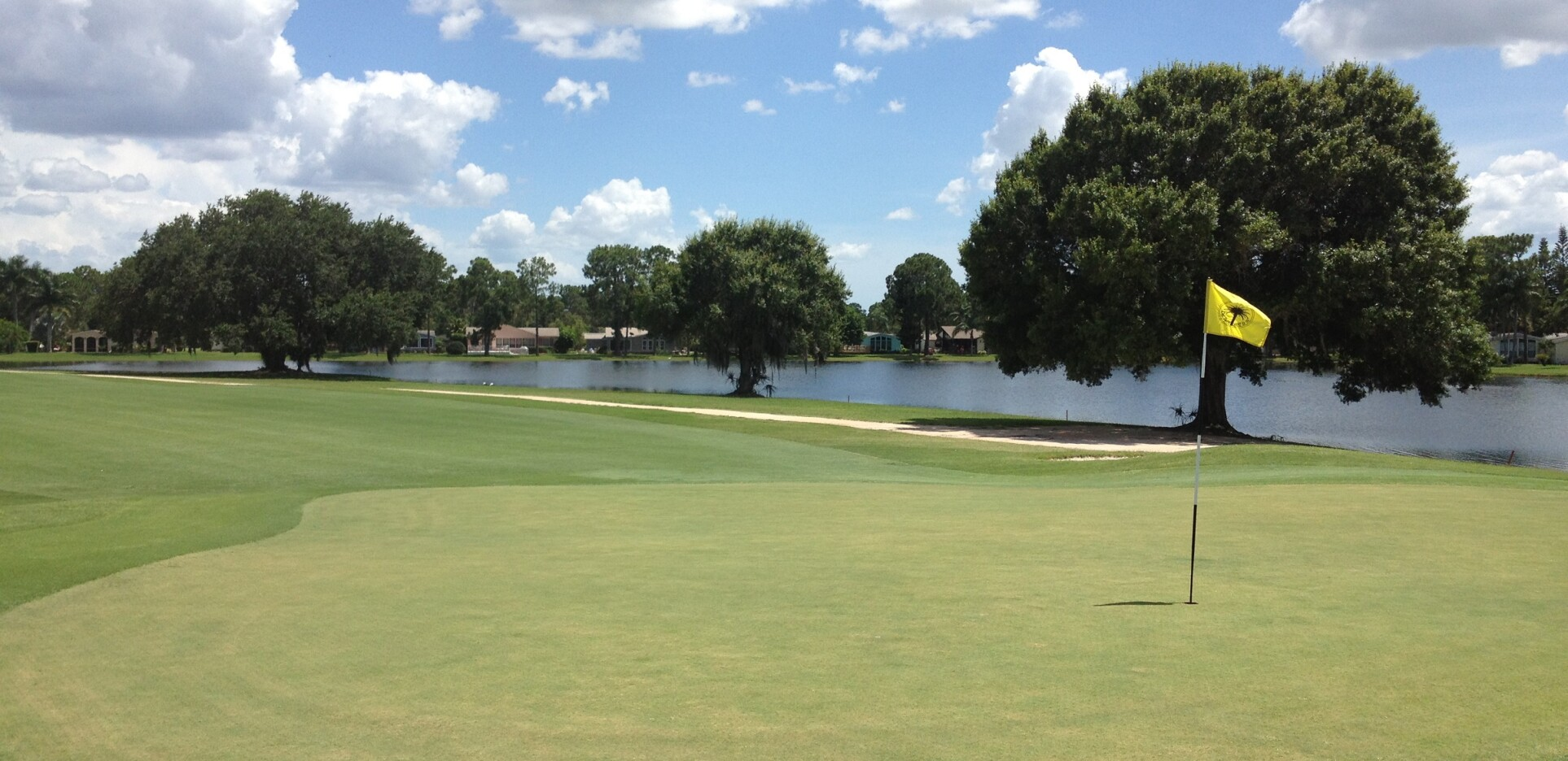 Del Tura hole with flagstick by lake