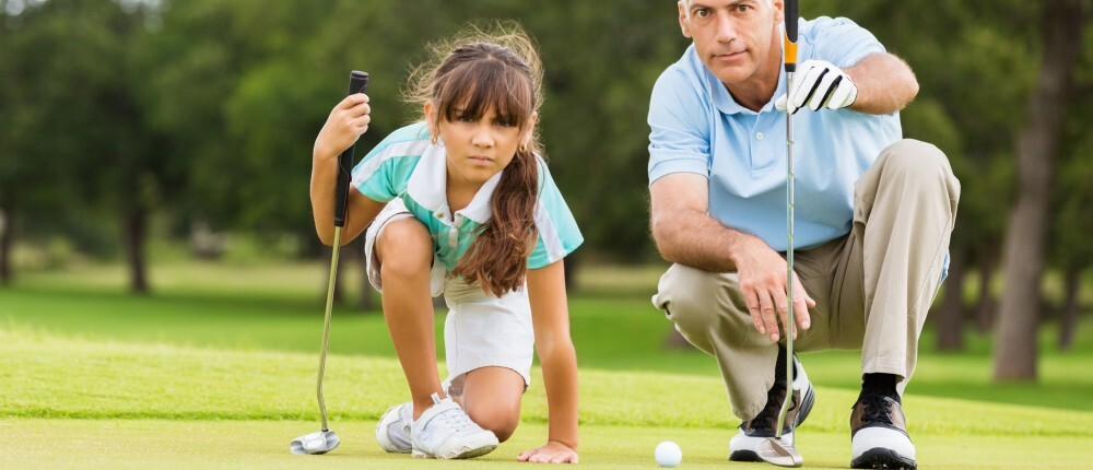 father teaching daughter golf on putting green