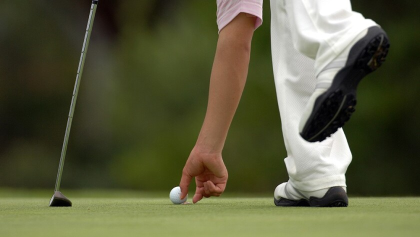 golfer picking up ball on the golf course