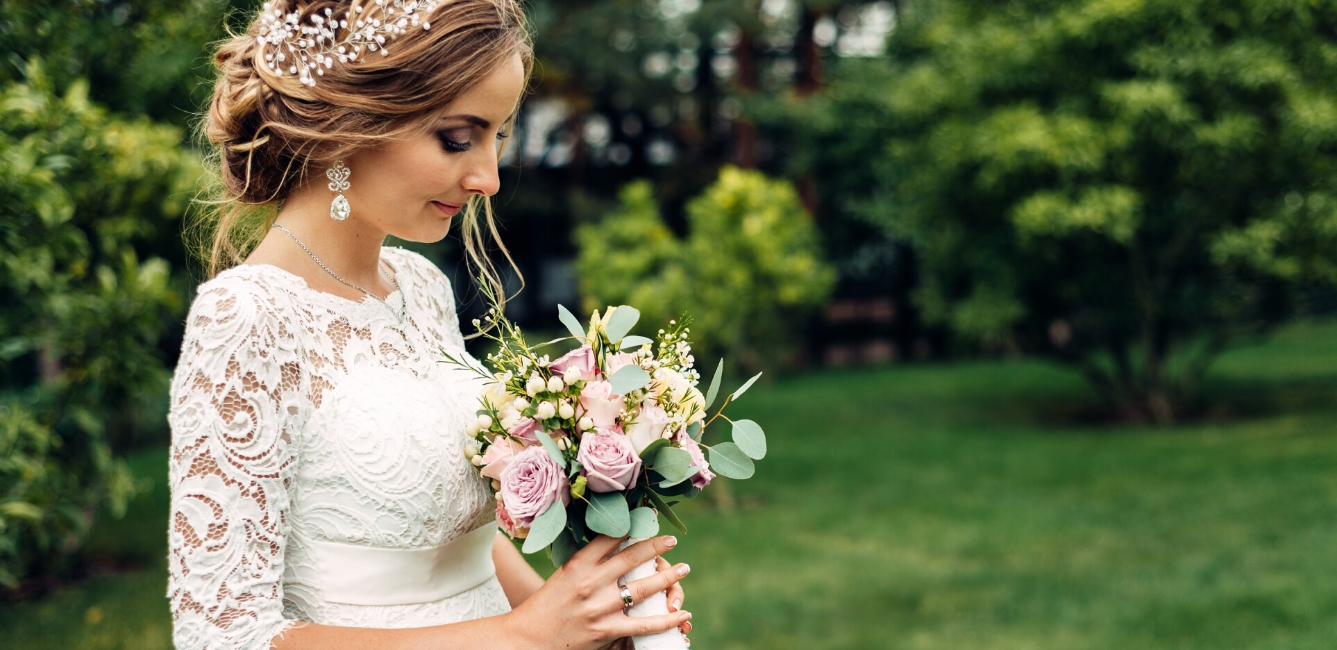 the bride in a white long dress with a wedding bouquet is standing alone and looks at a bouquet of flowers