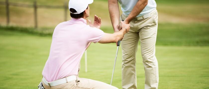 golf instructor teaching student grip