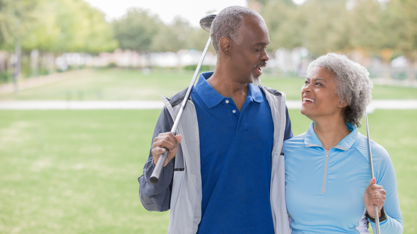 couple holding clubs on the golf course