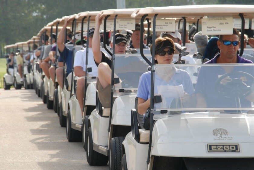 golf outing starting with golfers in golf carts lined up