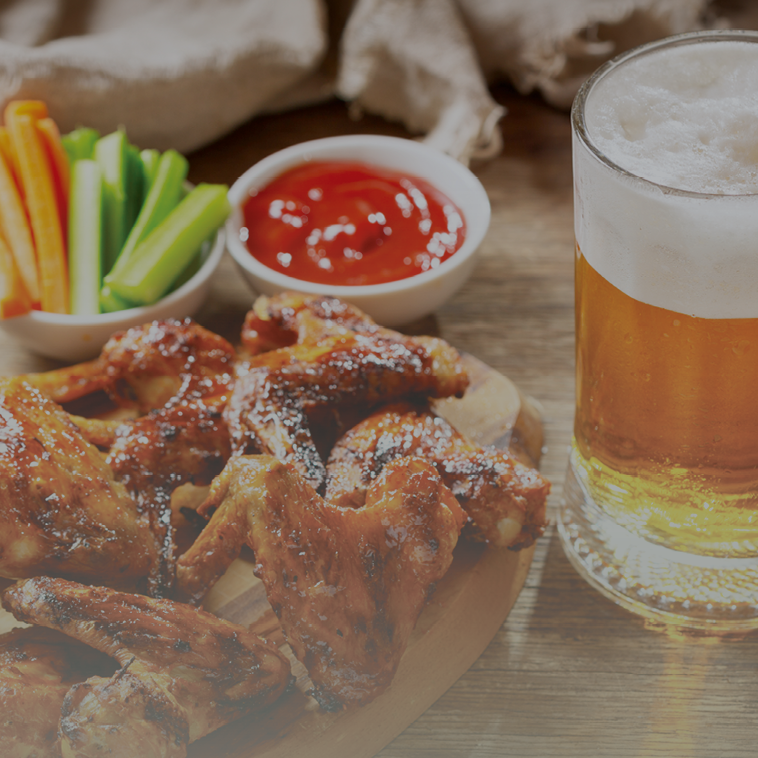 wings on wood platter with celery carrots and beer