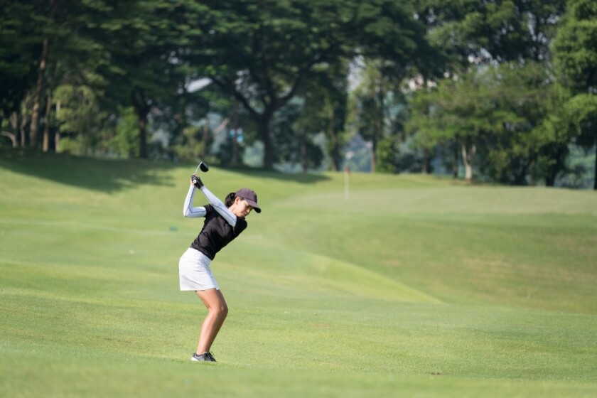 lady swinging club on golf course