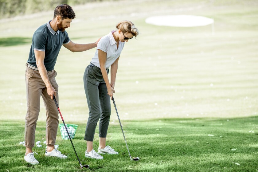 Woman with male instructor playing golf