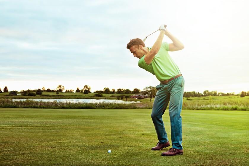 golfer swinging club on golf course