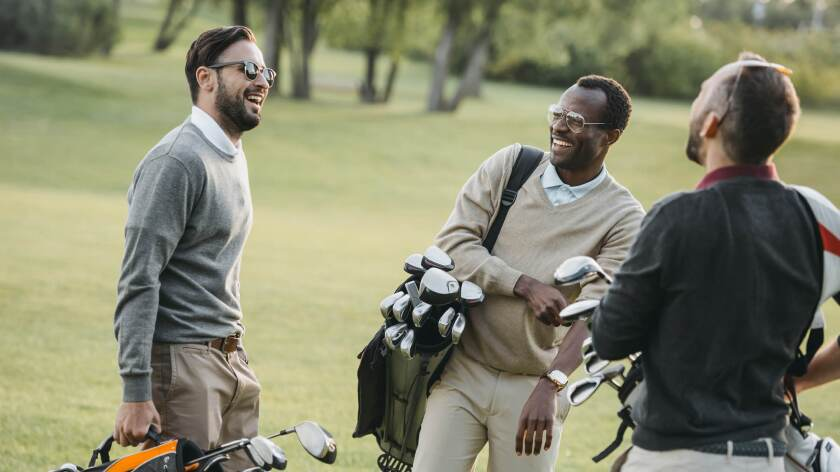threesome group of male golfers talking on golf course