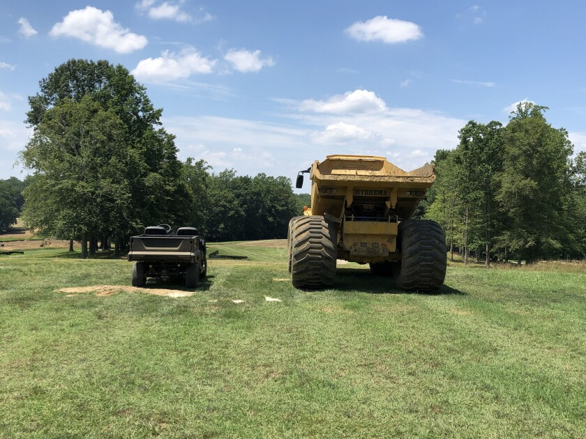 A size comparison between a maintenance golf cart and construction equipment used during the renovation of The Preserve at Eisenhower golf course
