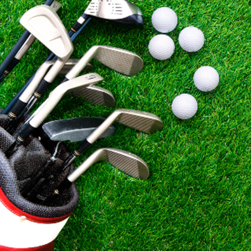 golf clubs and balls on grass