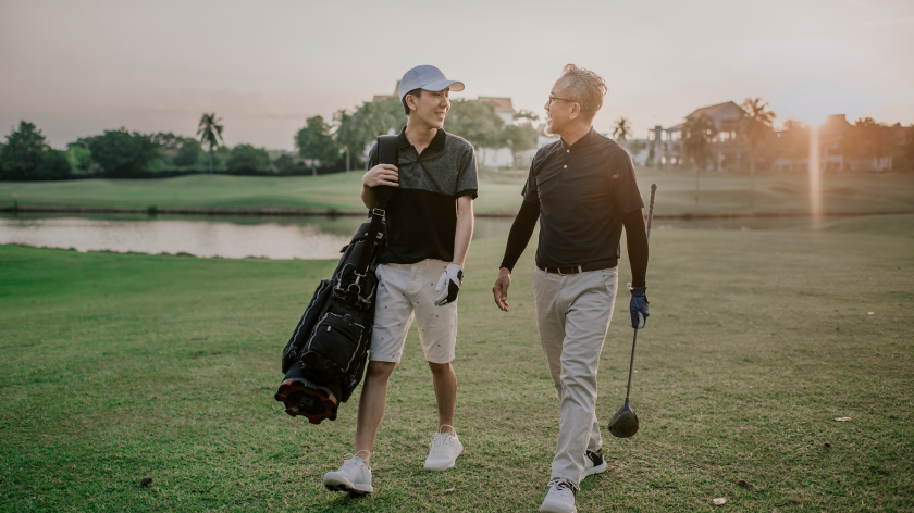 father son discussing golf game walking the course at sunset