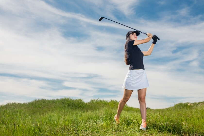 Girl Swinging a golf club