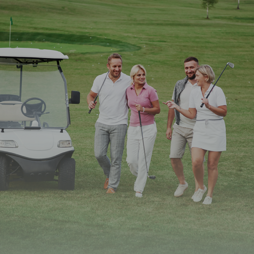 foursome of golfer couple holding clubs walking by golf cart