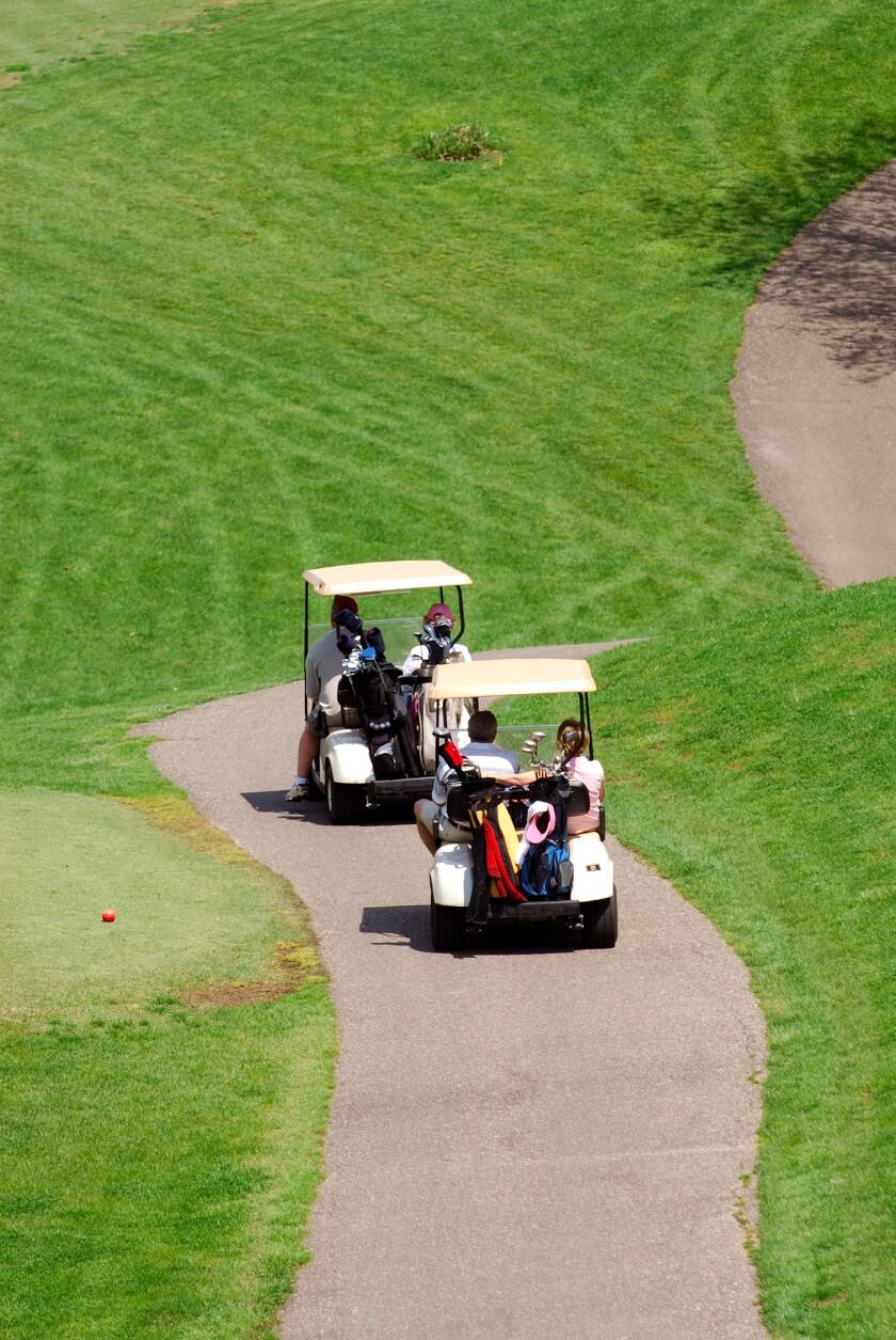 golfers driving golf carts down cart path