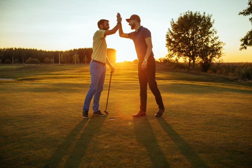 twosome guys on the golf course high fiving at sunset