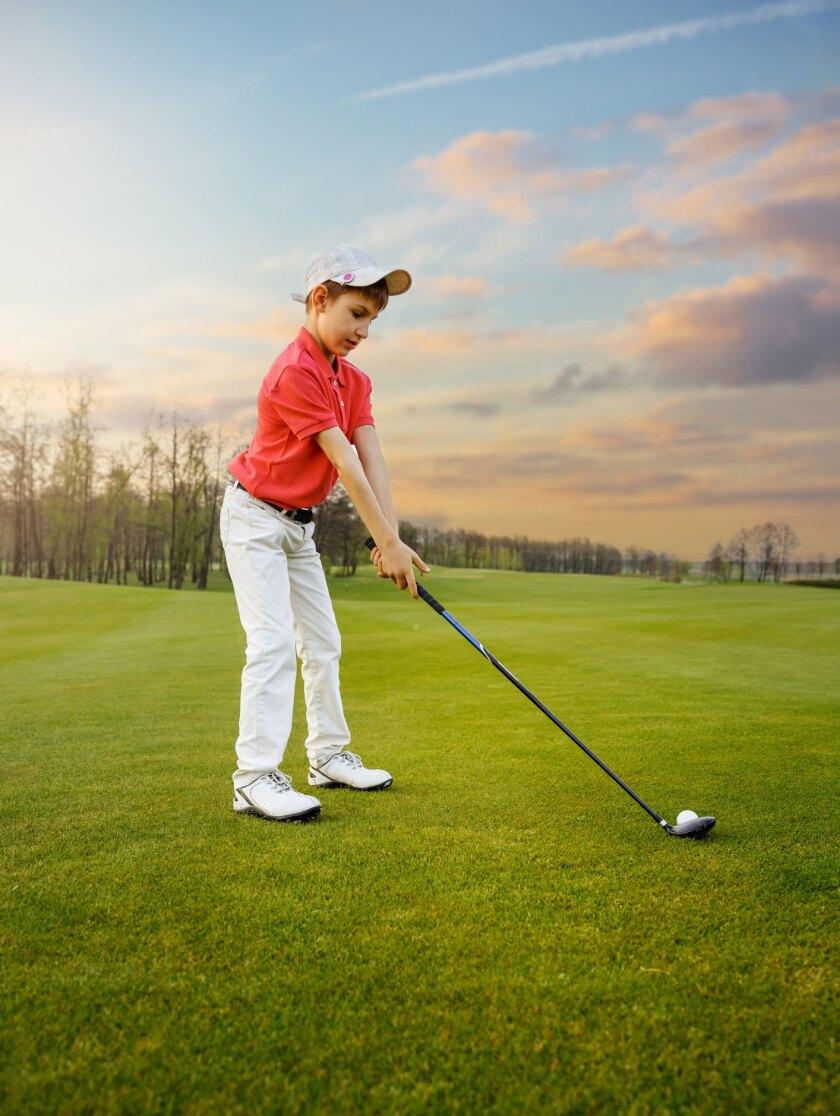 junior boy golfer teeing off on golf course