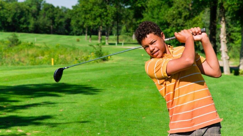 Junior golfer swinging on golf course