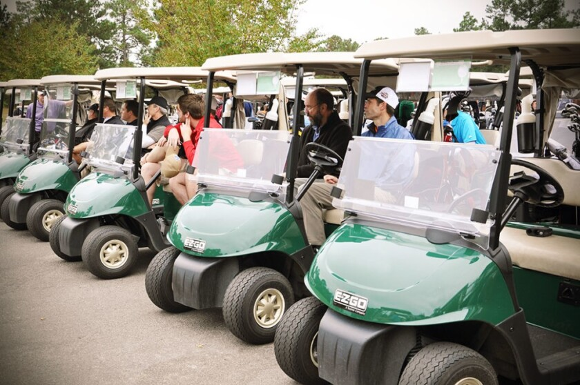 golf carts lined up for golf outing or tournament on the course