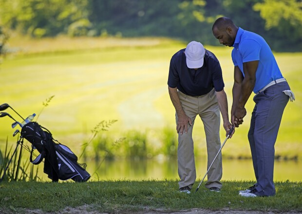 Golf Pro Teaching Male Golfer by pond