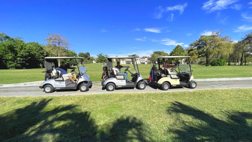 threesome in golf carts at Colony West Golf Club in Tamarac, Florida
