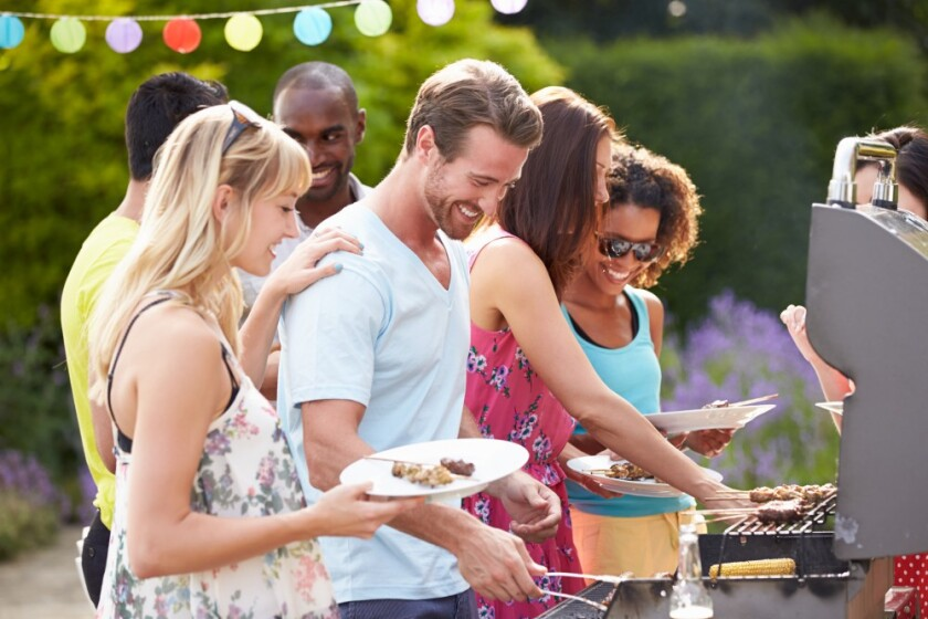 group of friends outside at bbq grill event eating