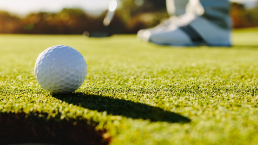 golf ball being putted on golf course in sunlight
