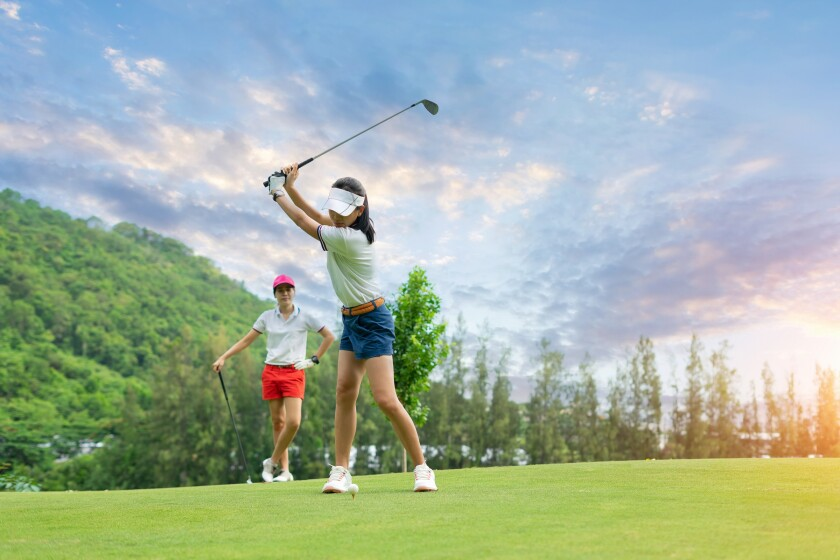 Golf ball on tee ready to be struck by woman golfer as partner watches with sunset