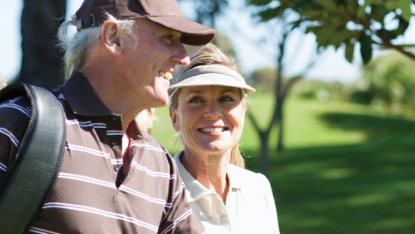 senior couple coed golfers on course