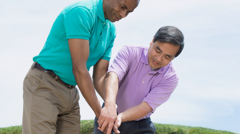 Asian golf instructor teaching adult Black man