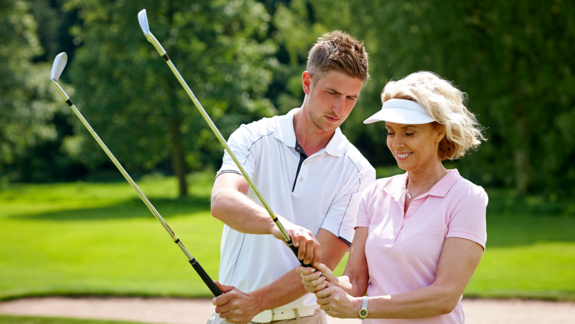 Golf instructor teaching student gripping on golf course