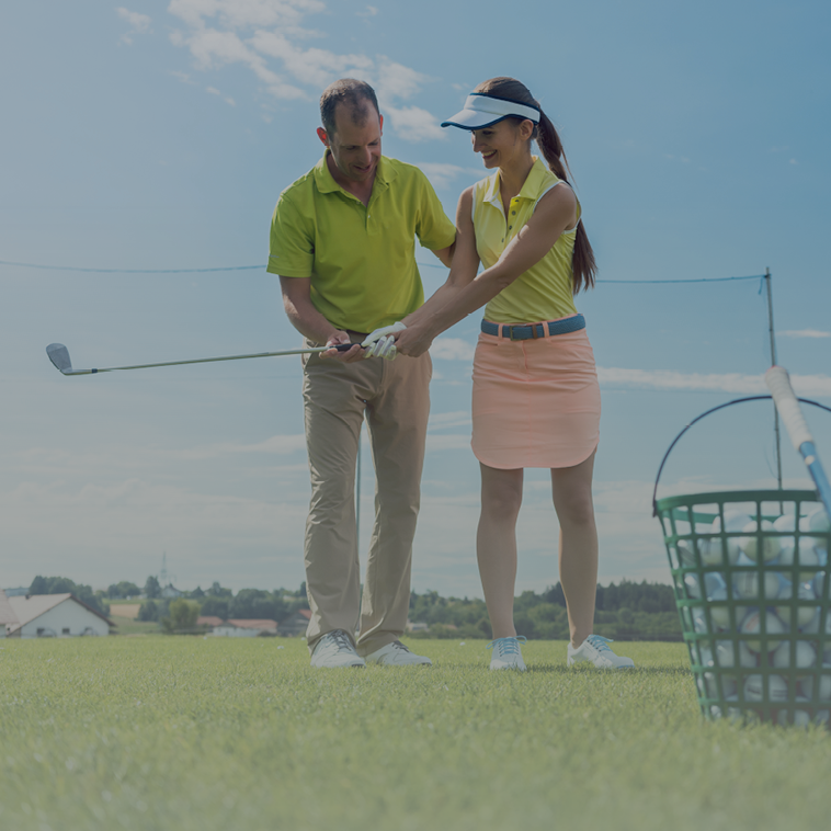 Golf instructor teaching student with range bucket