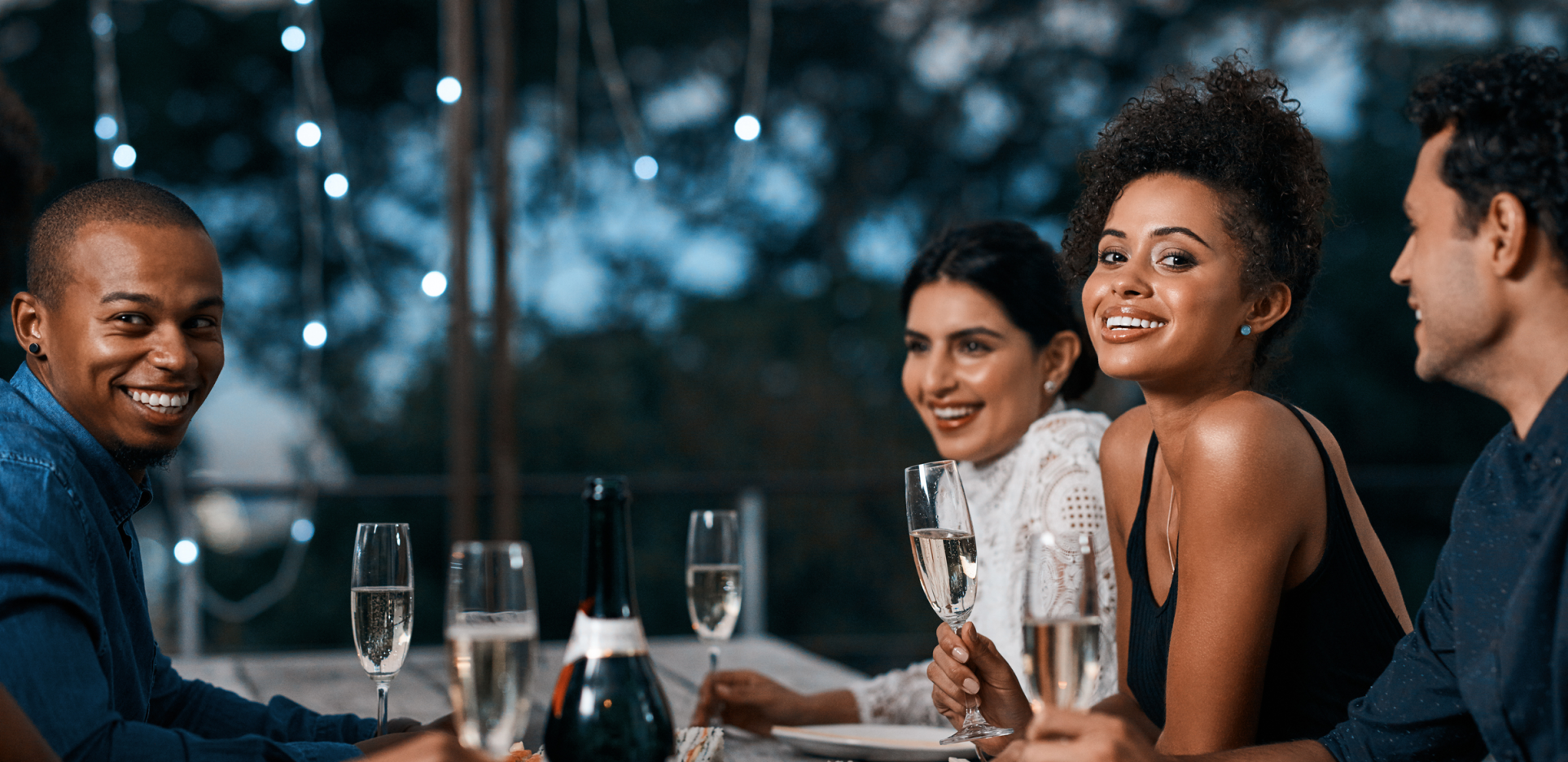 couples or group of friends celebrating with champagne at dinner